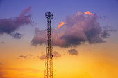 Telecommunication tower with antenna and technician working on sunset sky