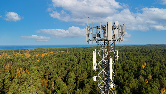 telecommunication tower with antennas for 5g network on forest and blue sky background. mobile internet broadcast