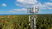 istock telecommunication tower with antennas for 5g network on forest and blue sky background. mobile internet broadcast 1282678515