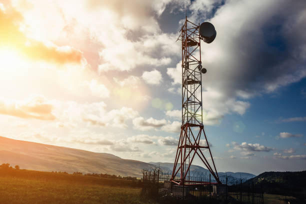 telecommunication tower with dish and mobile antenna on mountains at sunset sky background - ripetitore per telefoni cellulari foto e immagini stock