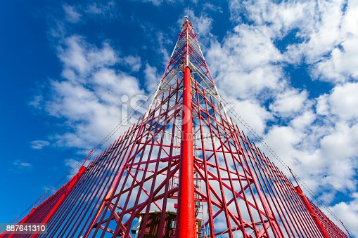istock Telecommunication tower with panel antennas and radio antennas and satellite dishes for mobile communications (2G, 3G, 4G, 5G) with red fence around tower against blue with clouds 887641310