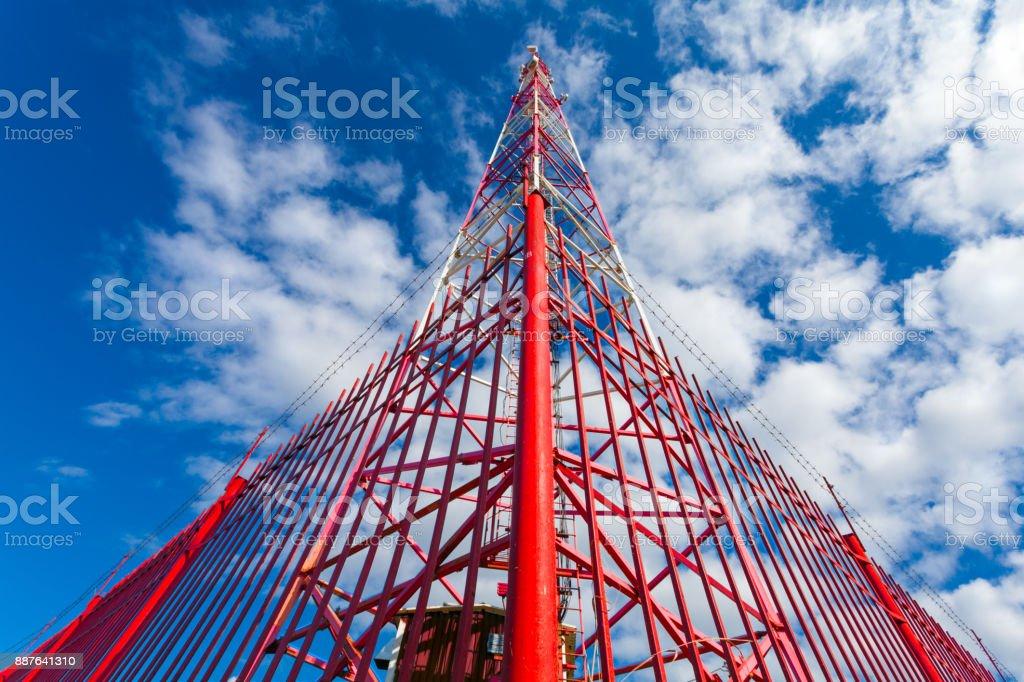 Fernmeldeturm mit Panel Antennen und Radio-Antennen und Satellitenschüsseln für Mobilfunk (2G, 3G, 4G, 5G) mit roten Zaun Turm gegen blau mit Wolken – Foto