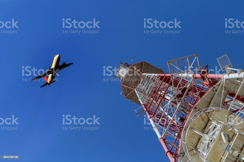 Telecommunications tower against blue sky, in red and white royalty-free stock photo