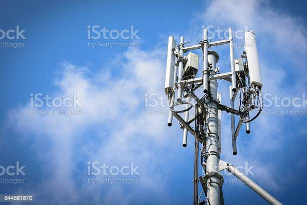 Telecommunications Tower with antennas on blue sky with cloud
