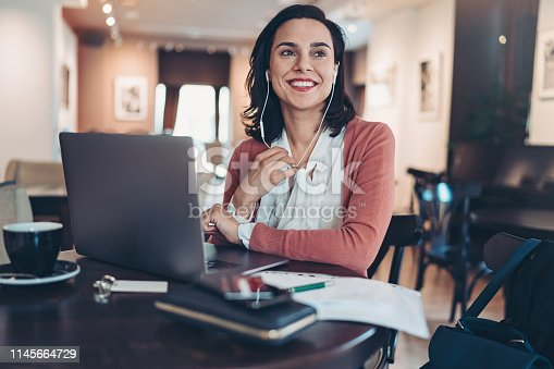 Businesswoman with laptop and headphones working in cafe