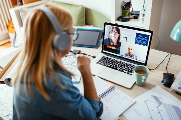 Teleconferencing - friends having video call during working hours stock photo