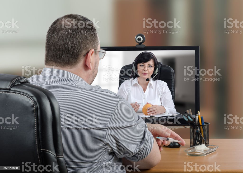 Telehealth patient is ready to insert the syringe into his skin stock photo