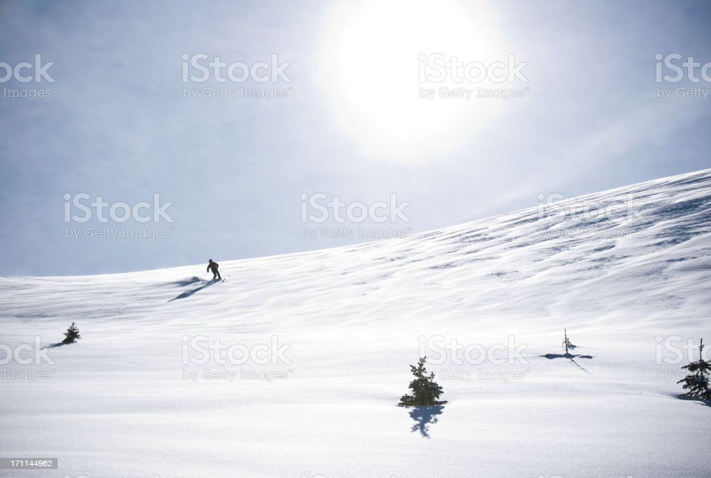 Telemark Skier Making Turn in Scenic Mountain Winter Landscape stock photo