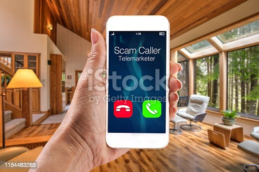 Telemarketer robocaller scam calling smartphone with woman holding telephone in house