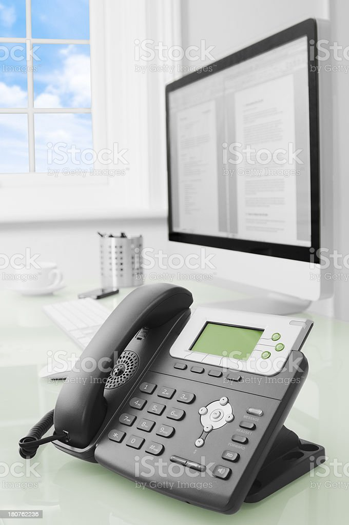 Telephone and computer on glass desk beside window royalty-free stock photo