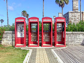 Bermuda - July 19, 2019: 4 red public call box also known as a telephone booth, furnished with a payphone and designed for a telephone user's convenience.