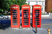 Eastbourne - UK, Aug 27, 2019: 3 red public call box also known as a telephone booth, furnished with a payphone and designed for a telephone user's convenience.
