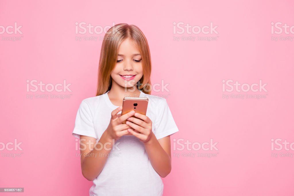 Telephone digital device people social networks pre teens concept. Portrait of charming addicted to phone cute sweet lovely adorable girl reading sending sms to friends isolated on pink background stock photo