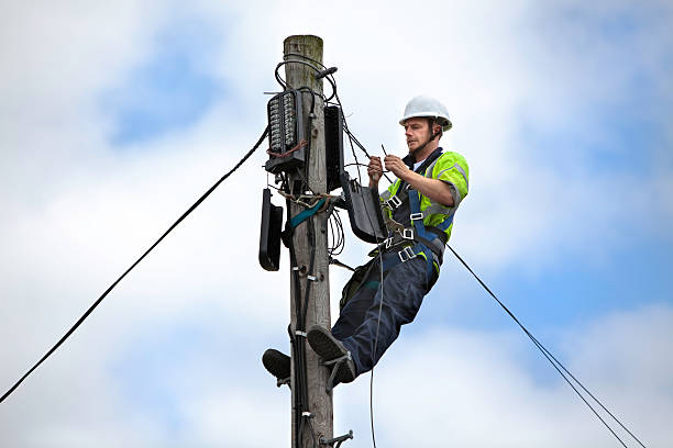 Telephone Engineer series Mid adult man working at the top of a telegraph pole telephone line stock pictures, royalty-free photos & images