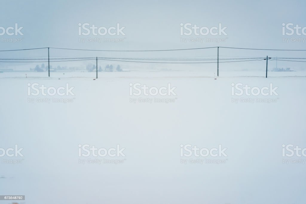 Telephone lines and small village in white snow field royalty-free stock photo