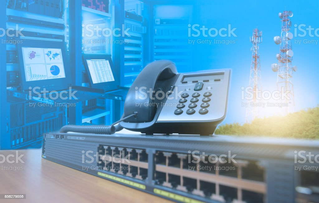 IP telephone on networking switch with blurred server rack cabinet data center room and telecommunication tower stock photo