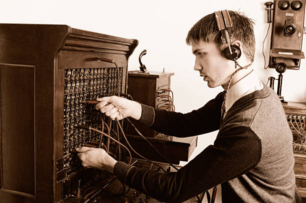 telephone operator using antique switchboard - switchboard operator stock photos and pictures