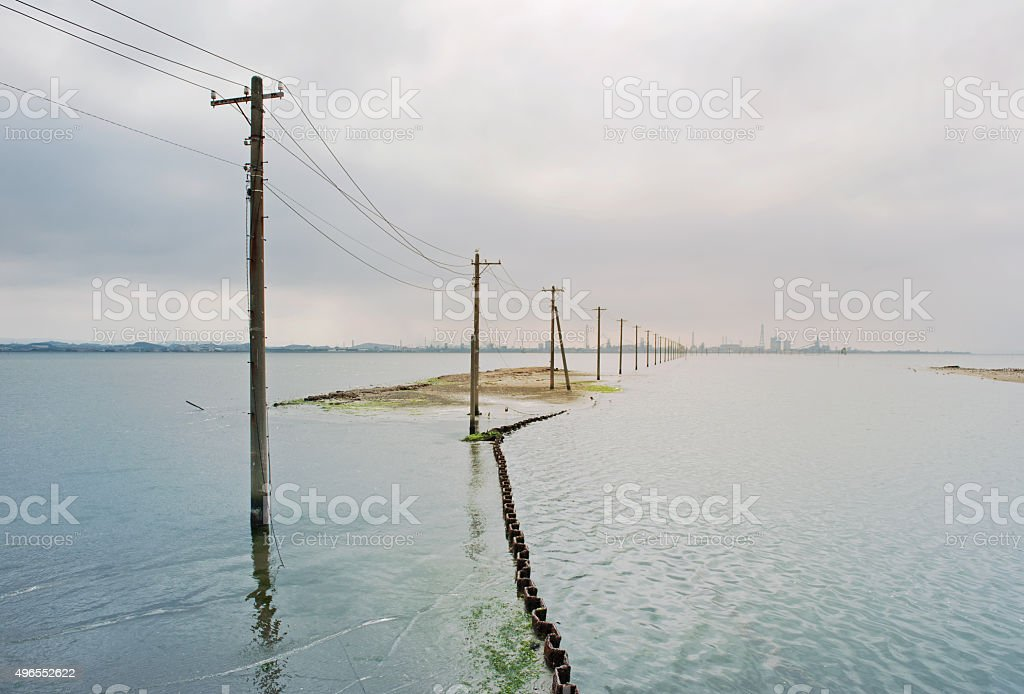 Telephone pole in the sea stock photo