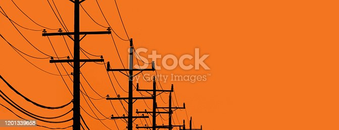 Telephone poles and wires in the distance with and orange background