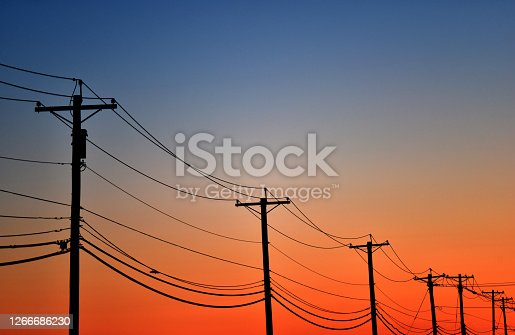 A line of telephone poles in front of a colorful sky at sunset.