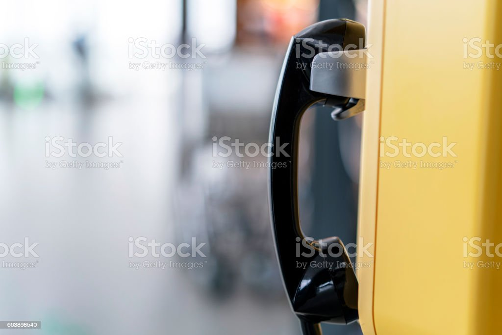 Telephone receiver hanging in telephone booth stock photo