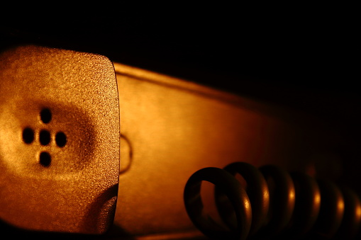 istock telephone receiver on a black background and warm lighting, detail of the telephone cable 1254445783