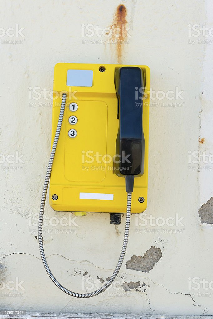 Telephone set mounted on a dilapidated wall royalty-free stock photo