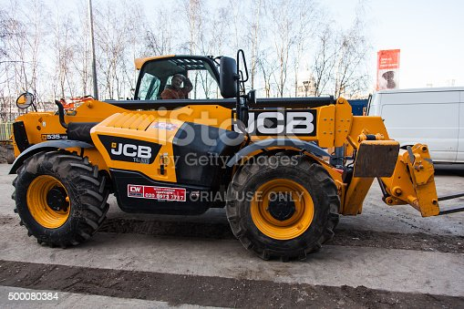 London, England - March 10, 2015: Construction site and a yellow JCB Forklift: Teleporter Telescopic Handler Loadall forklift. another vehical can be seen and a sign. The driver is in the cab of the forklift.