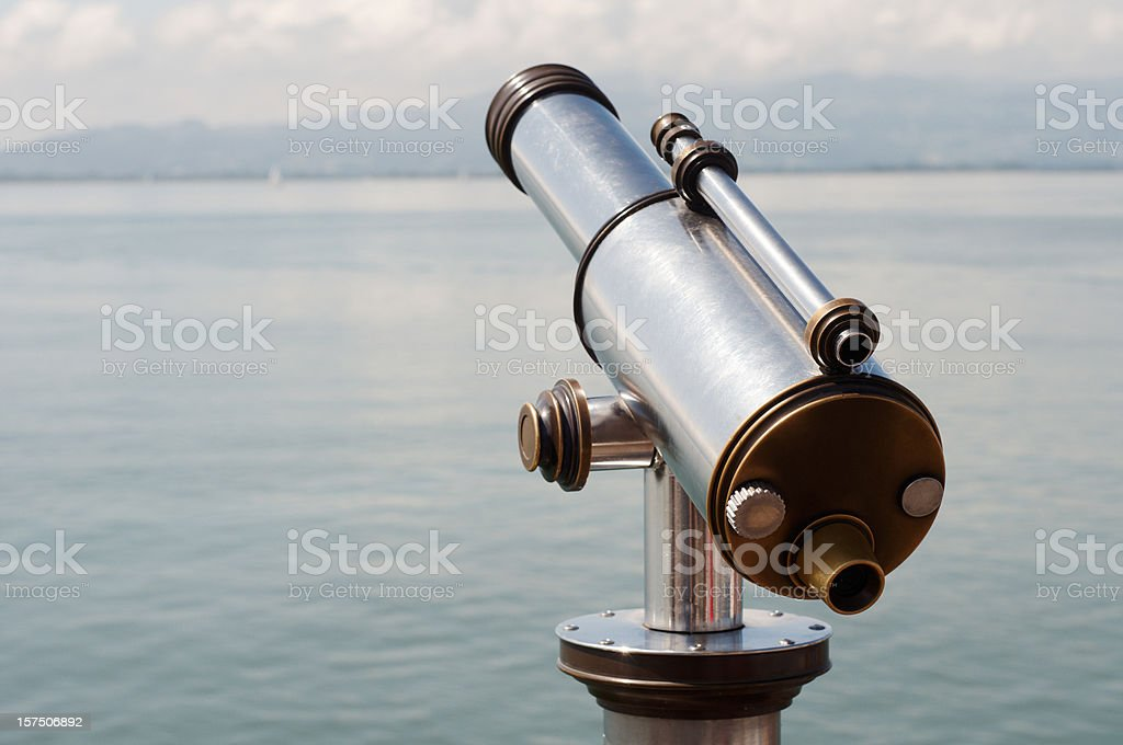 Telescope in front of a mountain lake royalty-free stock photo