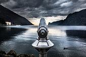 Telescope over Lake Garda in Italy. Overcast landscape on the background.