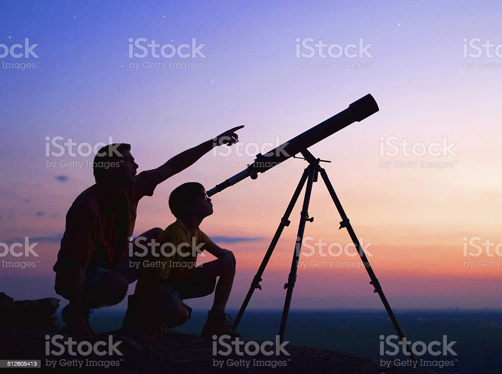 Telescope A young boy looking thru a telescope at sunset with his father. Aiming Stock Photo