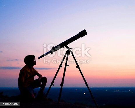 A young boy looking thru a telescope at sunset.