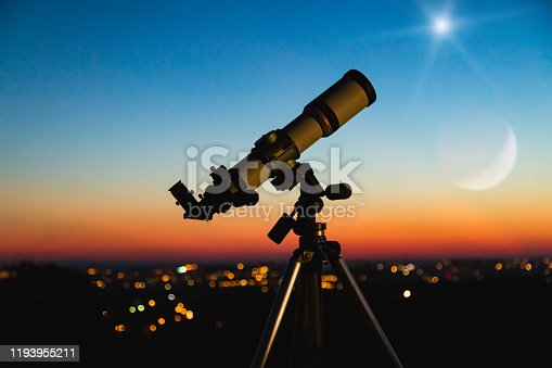 Telescope silhouette and night sky with city lights in the background.