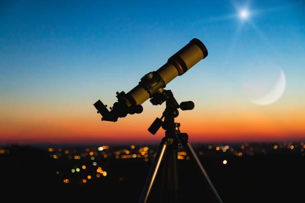 Teleskop-Silhouette und Nachthimmel mit Stadtlichtern im Hintergrund. – Foto