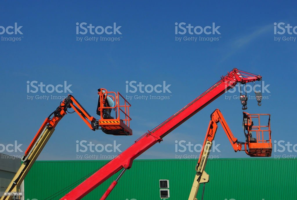 Telescopic crane and two aerial platforms of cherry pickers in a construction site stock photo
