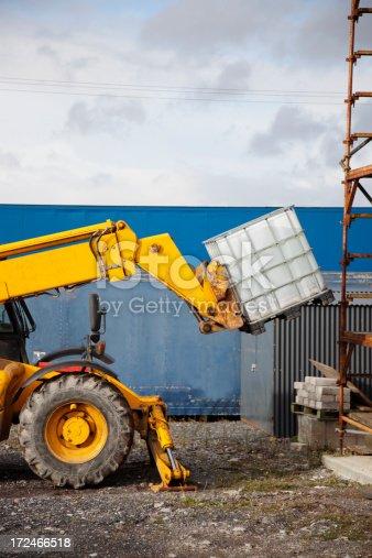 Telescopic handler vehicle lifting a heavy object.