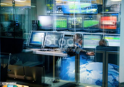 istock Television blurred background, news studio control panel with monitors through the glass 672418894