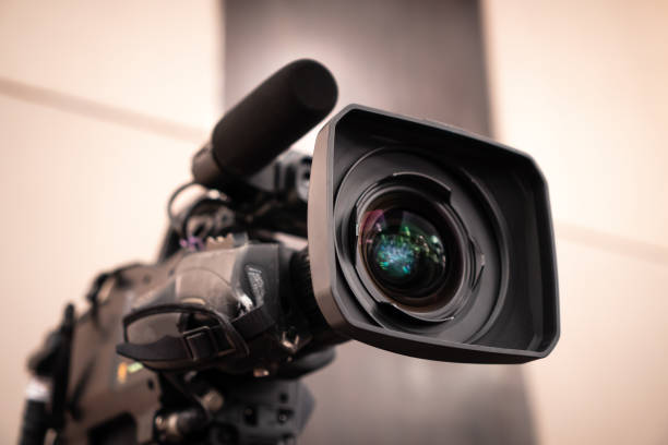 Television camera lens, Film of Video movie recording films shooting of grand opening in conference hall Live streming for presentation with bokeh light background. Media Production Concept stock photo