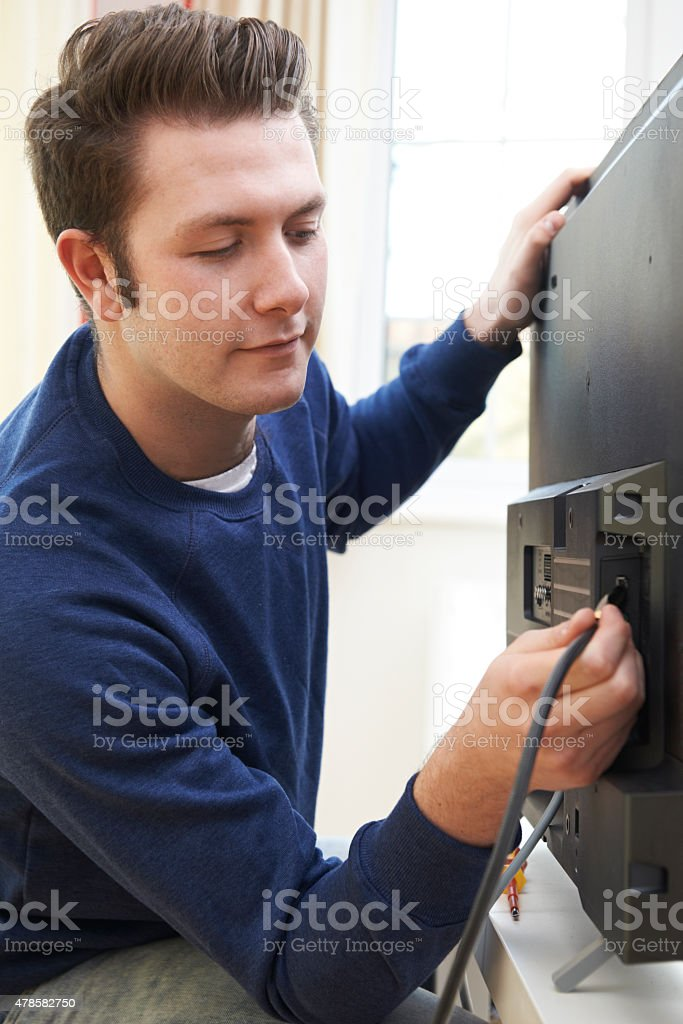 Television Engineer Installing New Television At Home stock photo