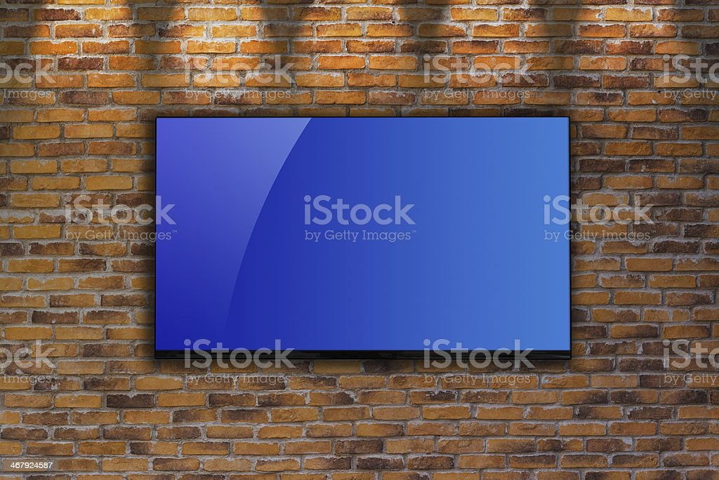 LCD television mounted on a brick wall royalty-free stock photo
