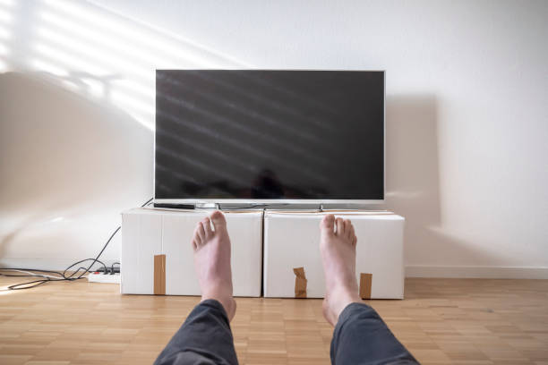Television on Cardboard Box in Bedroom and Men Legs stock photo