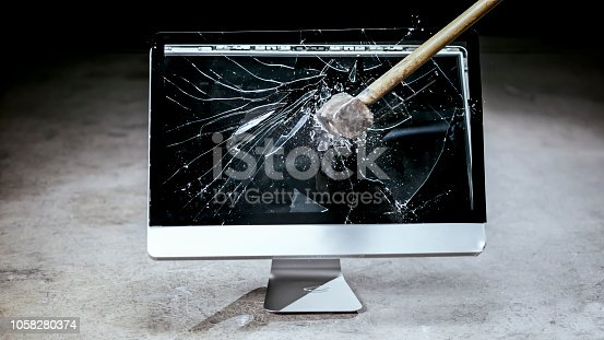 Close-up of hammer hitting on computer monitor.