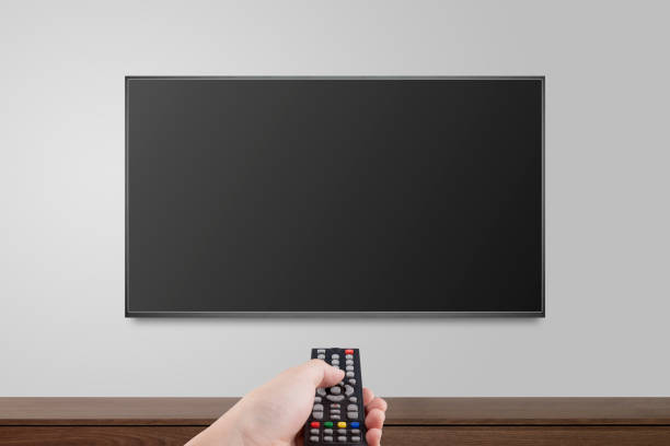 television on white wall with hand using remote control, tv 4k flat screen lcd or oled, plasma realistic illustration, black blank hd monitor mockup. - televisor imagens e fotografias de stock