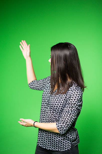 Television presenter recording in a green screen studio TV weather news reporter at work.News anchor presenting the world weather report.Television presenter recording in a green screen studio.Young woman with copy space on green screen chroma key anchor athlete stock pictures, royalty-free photos & images