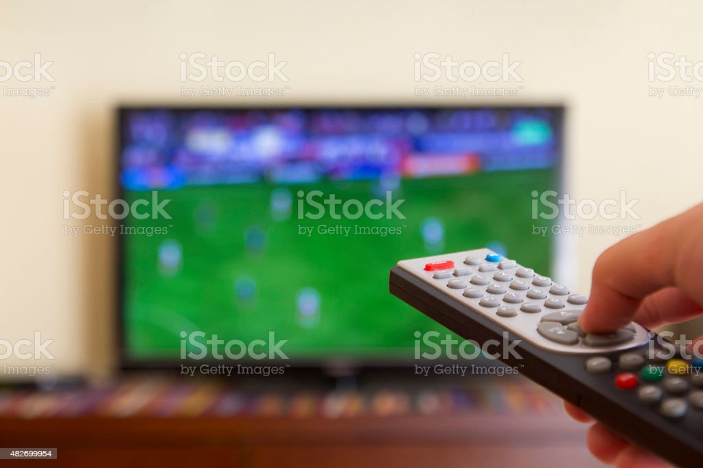 Television remote control in human hands stock photo