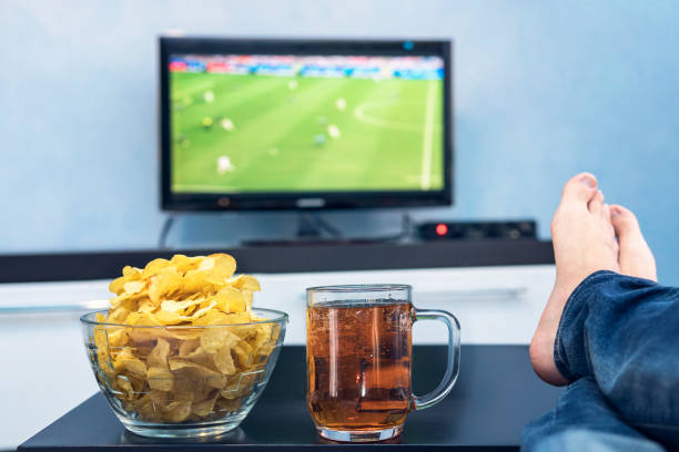 TV, television watching football match on TV with snacks and alcohol. relax in front of the TV. A fan of watching a football match play off. a plate of potato chips and a mug of beer on the table. stock photo