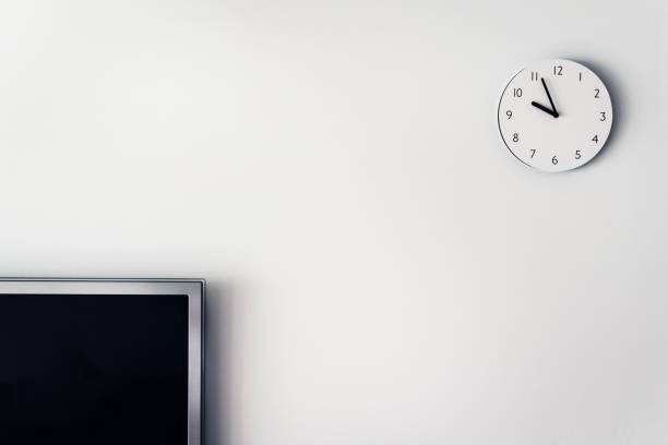 televison y círculo del reloj en la pared blanca. objeto interior de casa en casa. - wall clock fotografías e imágenes de stock