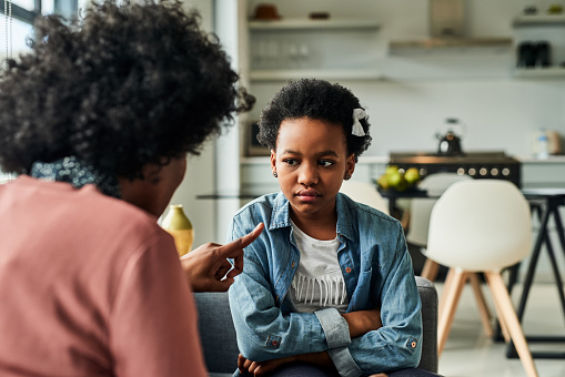Cropped shot of a young girl looking upset while being scolded by her mother