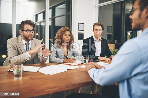 Shot of a group of businesspeople interviewing a candidate in an office