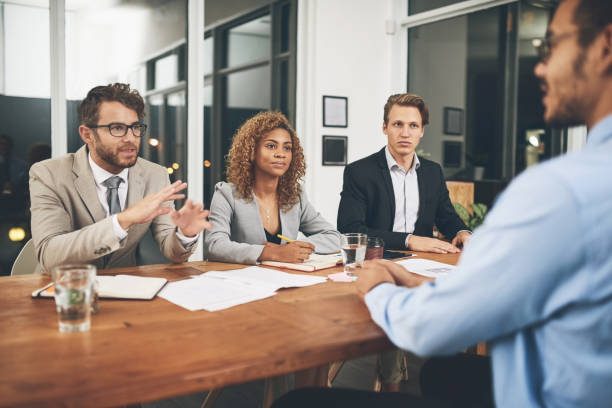 Tell us why we should hire you? Shot of a group of businesspeople interviewing a candidate in an office military recruit stock pictures, royalty-free photos & images